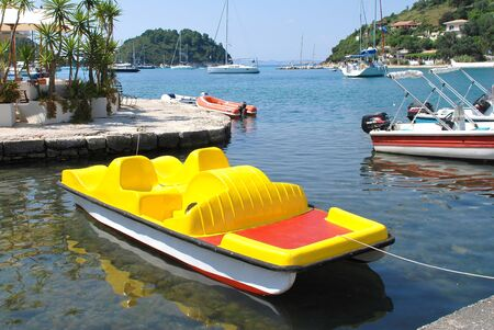 Paxos, Greece - June 10, 2014 - A bright yellow pedalo moored in the harbour at Lakka on the Greek island of Paxos. Just 13km long, the small Ionian island has a population of around 2300.