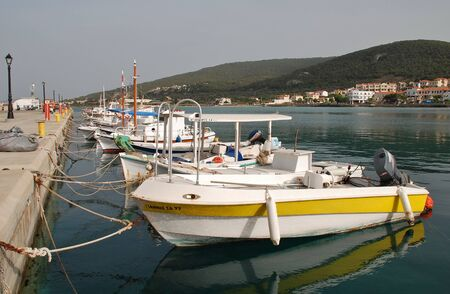 athenians: Agistri, Greece - May 12, 2016 - Small boats moored at Milos harbour on the Greek island of Agistri. Less than an hour from Piraeus, the small island is a popular destination for Athenians.