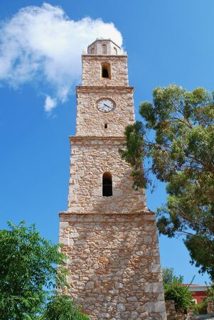 emborio: The old stone clock tower at Emborio on the Greek island of Halki. Broken for many years, the clock is always at twenty past four.
