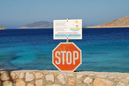 emborio: Halki, Greece - July 16, 2016 - A stop sign and sunbed price list at Ftenagia beach in Emborio on the Greek island of Halki. Tourism and fishing are the main industries of the small Dodecanese island.
