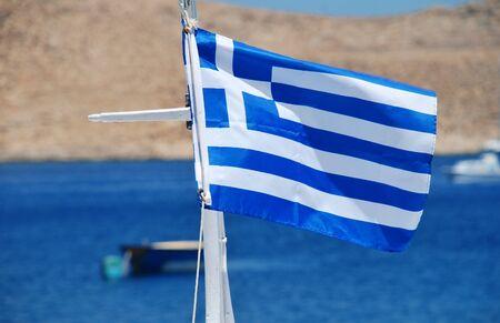 emborio: The National flag of Greece flying in Emborio harbour on the Greek island of Halki. Stock Photo
