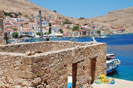 Halki, Greece - July 16, 2016 - A derelict stone building stands above Emborio harbour on the Greek island of Halki. One hour from Rhodes, the small Dodecanese island has a population of just under 300 people.