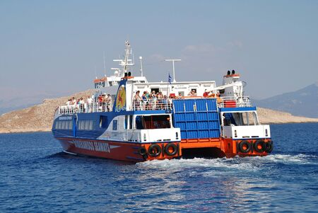 emborio: Halki, Greece - July 19, 2016 - Dodekanisos Seaways catamaran ferry Dodekanisos Express departs Emborio harbour on the Greek island of Halki. The 40mtr vessel was built in 2000 in Norway.