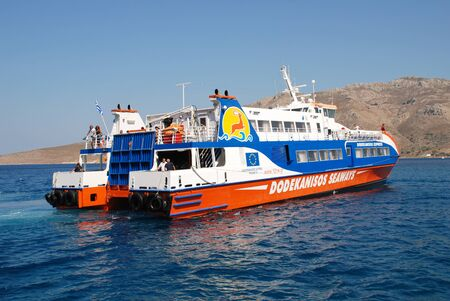 Tilos, Greece - July 19, 2016 - Dodekanisos Seaways catamaran ferry Dodekanisos Express arrives at Livadia harbour on the Greek island of Tilos. The 40mtr vessel was built in 2000 in Norway.