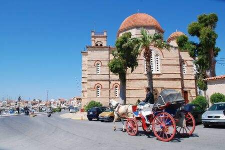 Aegina, Greece - April 26, 2017 - A horse and carriage giving rides to tourists passes the Panagitsa church on the harbour front of Aegina Town on the Greek island of Aegina. Editorial
