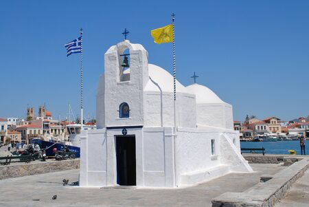 athenians: Aegina, Greece - April 26, 2017 - The whitewashed church of Agios Nikolaos on the harbour front at Aegina Town on the Greek island of Aegina. The island is a popular destination for Athenians. Editorial