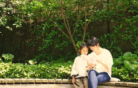 Mutter und Tochter , die am Park lesen Standard-Bild - 82218764