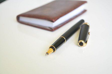 A pen and notebook on white background