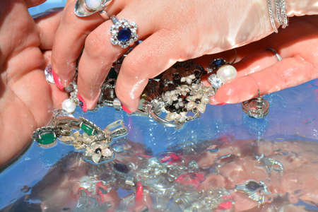 Woman hands and  jewelry on water background, pure water Stock Photo