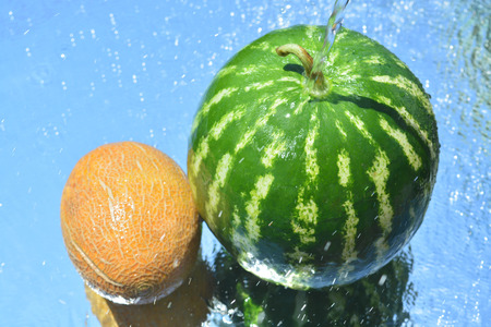 sliced watermelon: Watermelon and melon reflected in water