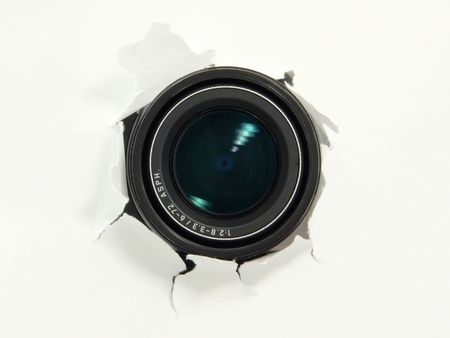 Digital camera object-glass uncovering from behind a paper wall, ready to take a snapshot.