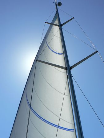 A view looking upwards at the mast, sail and rigging of a private yacht underway. Vertical perspective. Stock Photo