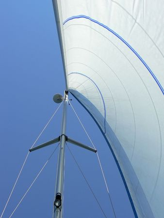 Yacht sail and mast with blue cloudless aky above.