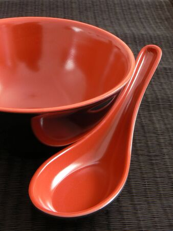 Still-life composition of a red and black plastic bowl with a matching spoon used for eating the japanese soup. Both objects on a black reed pad.