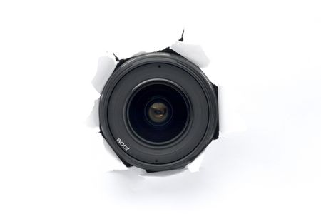 Camera lens sticking out of the white (paper) wall, ready to take a snapshot. Close up. Spy concept. Stock Photo