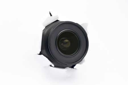 Camera lens sticking out of the white (paper) wall, ready to take a snapshot. Close up. Spy concept. All lettering retouched off the outer lens ring to allow better image flipping.