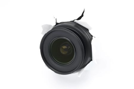 Camera lens sticking out of the white (paper) wall, ready to take a snapshot. Close up. Spy concept. Lens designation and lettering retouched off the outer lens ring to support easy image flipping.