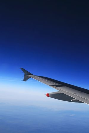 Left wing of the aircraft over clear and cloudless sky. Free space for custom text above the wing. Stock Photo