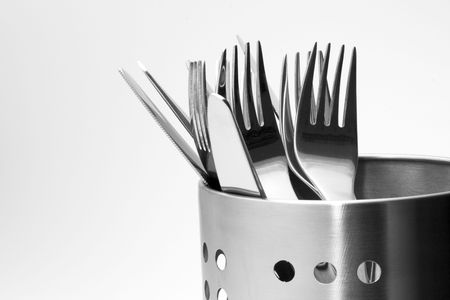 Detailed view on a polished cutlery in aluminium perforated stand isolated on white background