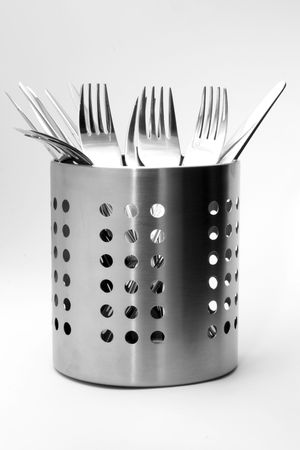 Fancy silver cutlery in a decent stand photo