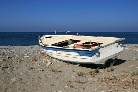 Low angle view at an old boat lying on the beach with some junk in the sand over cloudless sky. Stock Photo