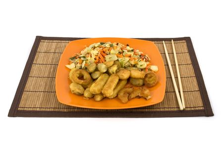Plate full of seafood and chopsticks on a natural reed pad. Isolated on pure white. photo