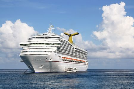 Anchored luxury cruise ship on a day with cloudy sky but calm seas.