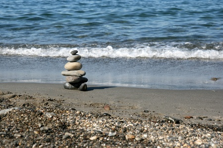 Stacked stones representing the zen symbol on the beach. Focus on the stones.