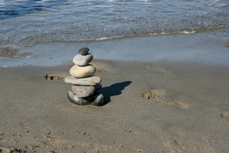 Pile of stones and footprints in the wet sand on the beach. Peaceful meditation concept. photo