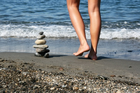 eastern philosophy: Female walking on the beach around a pile od stoned arranged as a Zen symbol