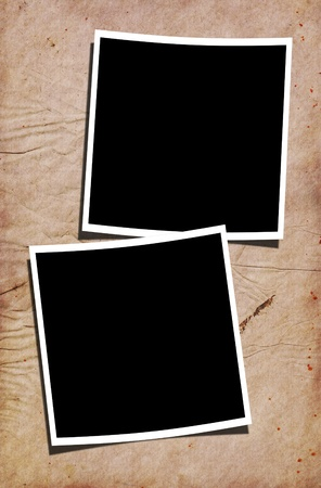 splotchy: Two blank polaroid photographs on creased stained paper background.