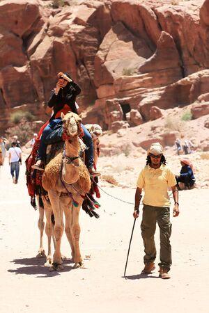Petra, Jordan - June 18, 2010: A tourist riding a camel and taking photos in beautiful Valley June 18 in Petra, Jordan. Cameleer walking next to the camel. Editorial