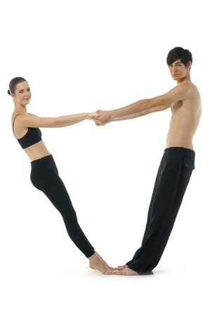Couple gymnasts practicing a complex double yoga pose.