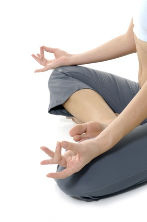 lotus pose: Close up of womans hand resting on her knee with fingers in yoga meditation pose