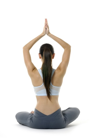 moves: Young woman doing yoga moves or meditating on white