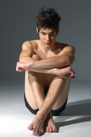 young muscular man, sitting, studio shot photo