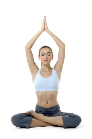 Young woman doing yoga moves or meditating on white