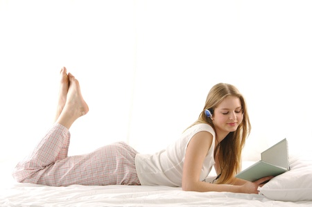 foot girl: happy girl reading book and listening music isolated on bed