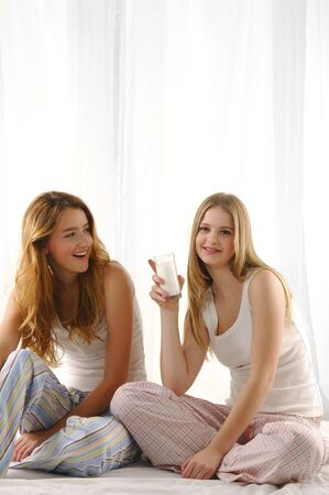 Two lovely friends with one glass of milk   photo