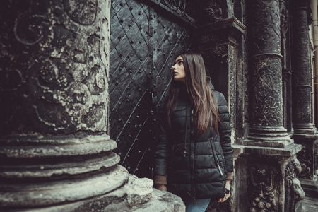 The young girl stands on the background of the old gothic wall.