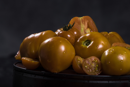 yellow tomatoes  composition on black isolated  background ,  many brand
