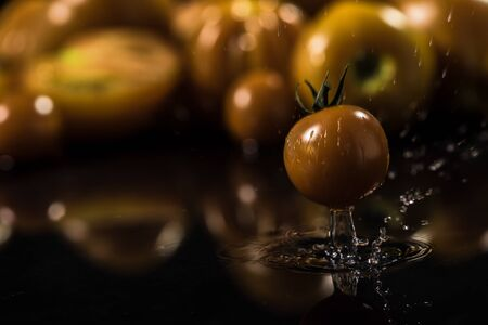 Yellow tomatoes on black background ,water drops ,closeup ,  mirror