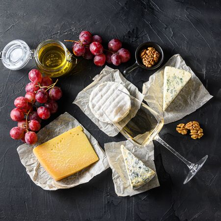 Cheese appetizer snacks french cheese, glass sauvignon wine on the blackboard square.