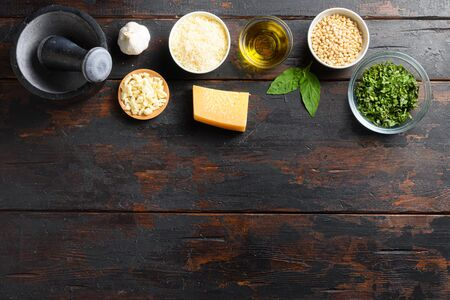 Fresh ingredients for pesto genovese Italian food cooking ingredients on dark background with rustic wooden chopping board, top view, copy space on bottom. Stok Fotoğraf