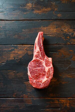 Raw cowboy steak on Rustic dark old wooden backdrop. Food preparation top view space for text