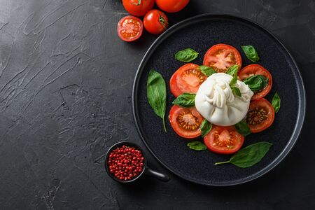 Burrata, Italian fresh cheese made from cream and milk of buffalo or cow. on black plate over black stone surface top view space for text.