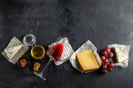 Assortment of cheeses, Camembert antipasto a glass of red wine, honey, nuts and spices, on a black backdrop stone slate Top view. Free space for text top view.