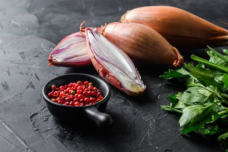 Organic shallot, eschalot or scallion raw ripe onions with greens and rose peppercorns sliced and halved black concrete textured background side view selective focus space for text.