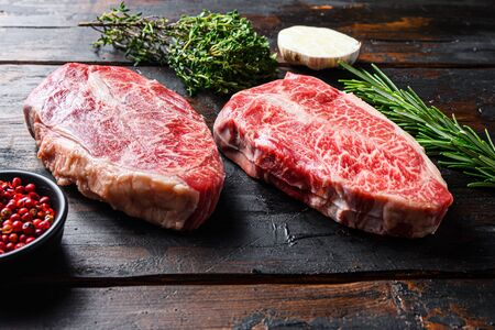 Top blade cut Steak or Feather steak raw meat over old wood table background. Side view.