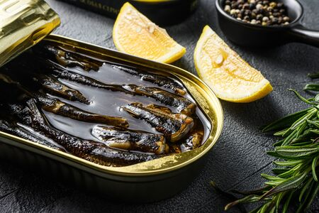 Top viTop view of opened cans with sprats on grey textured stone table,with herbs rosemary